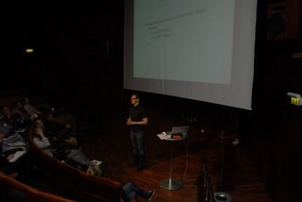 Jag står framför en stor projektorduk och talar till publiken
